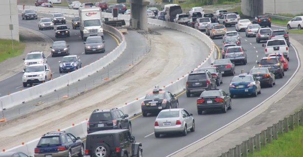 Busy highway: Busy highway with automobiles, cars, vans, trucks: Insurance rates higher in Ontario: Strype Injury Lawyers